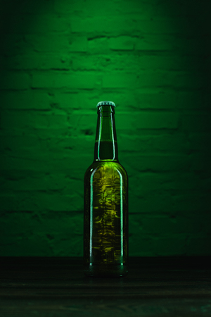 close-up view of single green glass bottle of fresh cold beer in green light