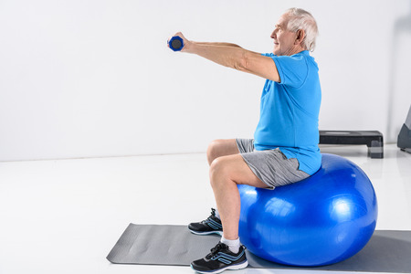 side view of senior man with dumbbells exercising on fitness ball on grey backdrop