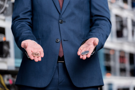 cropped shot of businessman holding bitcoins at cryptocurrency mining farm