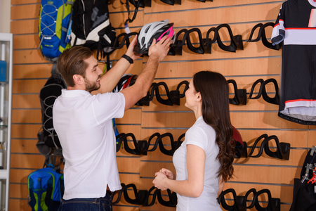smiling young bicycle shop workers arranging helmets on shelves
