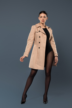 Woman in black pantyhose and heel shoes wearing trench on dark background Stock Photo