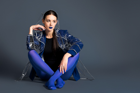 Slim woman in blue pantyhose and raincoat sitting on dark background 스톡 콘텐츠