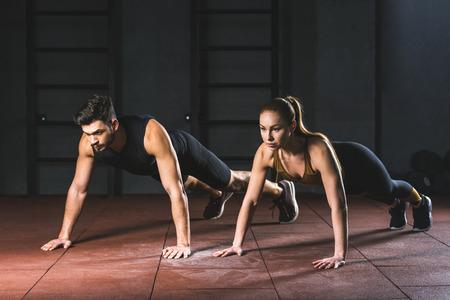 Sportvrouw en sportman doen push-ups in de sportschool in de sporthal