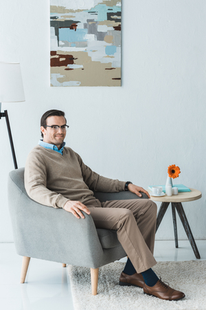 Man wearing casual clothes sitting in chair