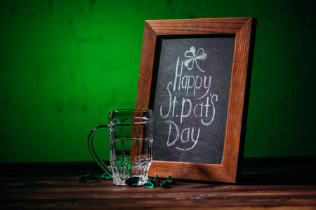 wooden frame with happy st patricks day inscription and empty beer glass on table Stok Fotoğraf