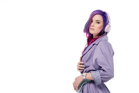 attractive young woman in purple trench coat and headphones isolated on white