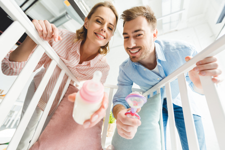 Low angle view of smiling parents with feeding bottle and toy
