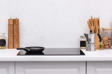 frying pan on induction panel at modern kitchen in front of blank white wall Stock Photo