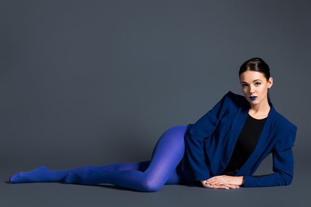 Girl in blue clothes lying on dark background