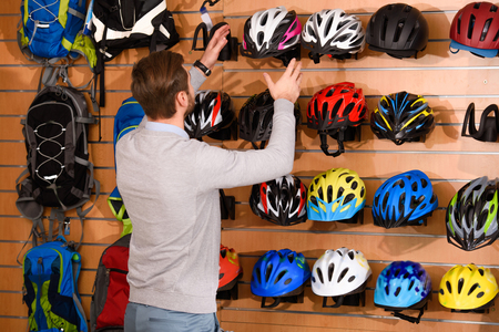 back view of young man choosing bicycle helmets in bike shop Stock Photo
