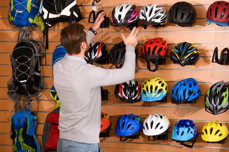 back view of young man choosing bicycle helmets in bike shop Stock fotó