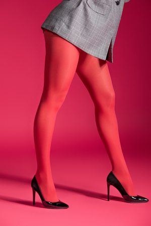 Cropped view of woman wearing red tights and grey jacket on red background Stock Photo