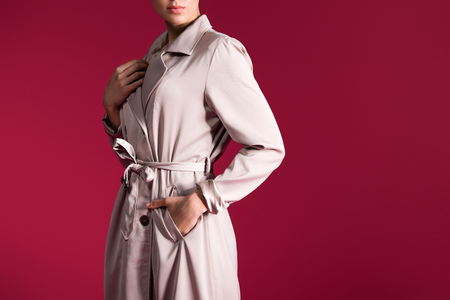 Cropped view of woman in beige trench isolated on red background