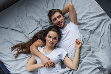 Smiling couple tenderly embracing while lying in bed Standard-Bild - 112312585