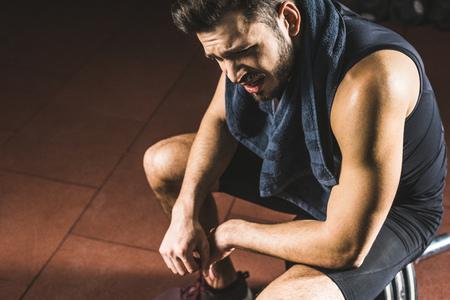 Veduta dall'alto di un giovane sportivo sconvolto seduto sul bilanciere in palestra