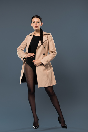 Slim woman in black pantyhose and beige trench on dark background