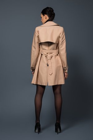 Rear view of woman in black pantyhose and beige trench on dark background 免版税图像