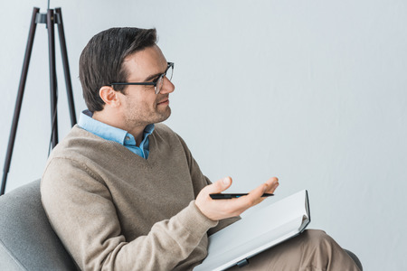 Male therapist in glasses listening to patient in office Stock Photo