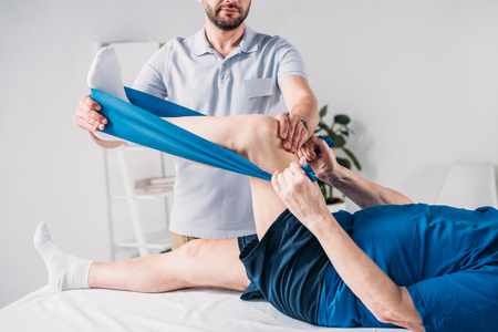 cropped shot of rehabilitation therapist assisting senior man exercising with rubber tape on massage table