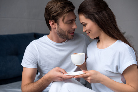 Beautiful young couple drinking coffee in bed Standard-Bild - 112312813