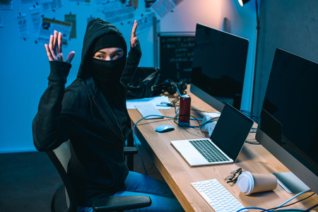 busted hacker in mask with raised hands in front of workplace