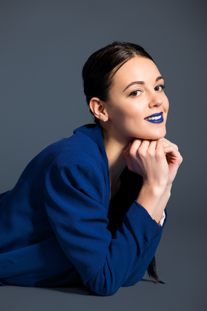 Smiling girl with blue lipstick wearing blue jacket on dark background