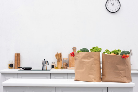 grocery store bags with vegetables on table at kitchen Stock Photo
