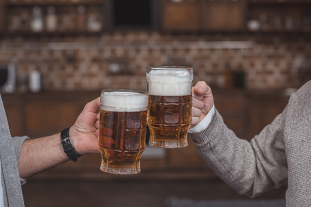 cropped image of adult son and senior father clinking with beer glasses at home Reklamní fotografie