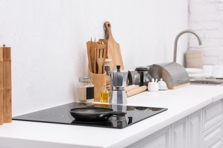 frying pan on induction panel at modern kitchen with various utensils Stock Photo