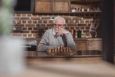thoughtful handsome grey hair man thinking and looking at chessboard at home