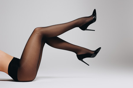 Female thin legs in black nylon tights and heel shoes on grey background