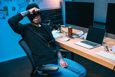 young female hacker at workplace taking off mask
