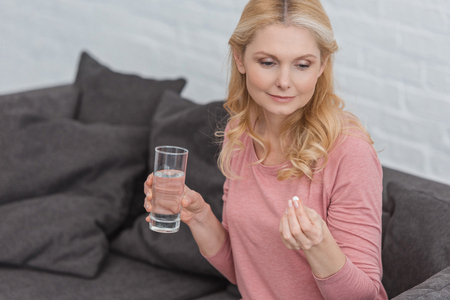 portrait of mature woman with glass of water and medicine in hands Stok Fotoğraf