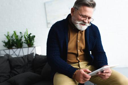 Homme senior barbu souriant à lunettes à l'aide d'une tablette numérique à la maison