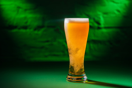 close-up view of glass with beer in green light, saint patricks day concept Stock Photo