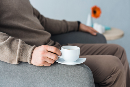 Close-up view of coffee cup in male hand on chair