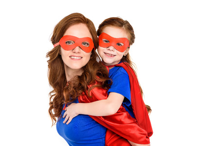 super mother piggybacking adorable daughter in mask and cloak and smiling at camera isolated on white
