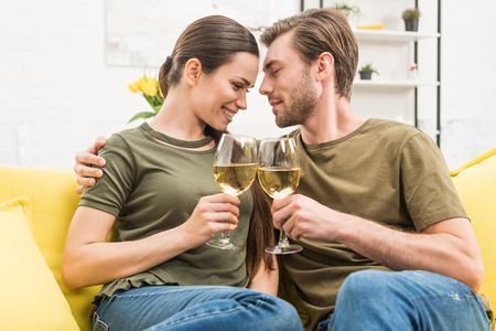 young cuddling couple drinking wine together on couch at home