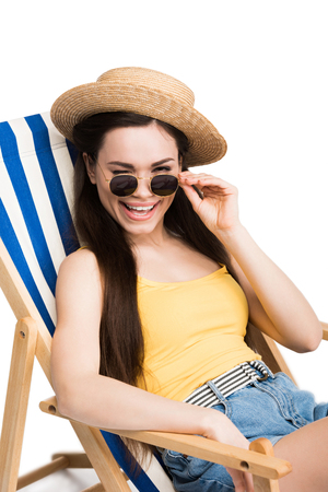 beautiful happy girl in sunglasses winking and relaxing on beach chair, isolated on white