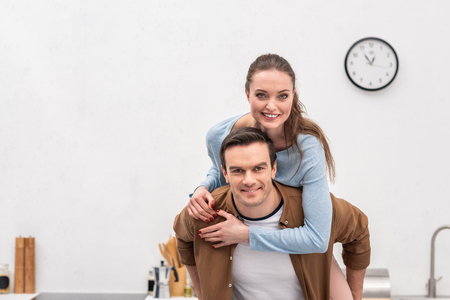 happy wife piggybacking on husband at home and looking at camera Stock Photo