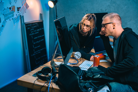 thoughtful couple of hackers looking at computer screen together in dark room