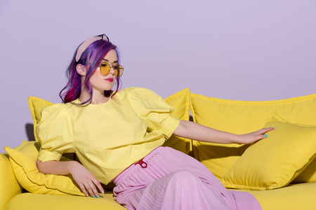beautiful young woman in yellow eyeglasses sitting on yellow couch