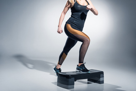Young woman exercising on step platform on grey background Stockfoto