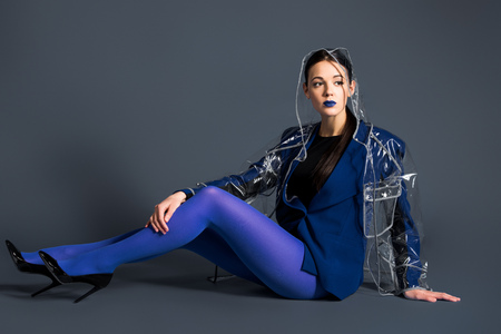Slim woman in blue pantyhose and raincoat lying on dark background Stock Photo