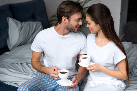 Smiling wife and husband drinking coffee in bed Standard-Bild - 112313873