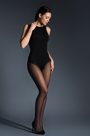Slim woman in black pantyhose and bodysuit on dark background 免版税图像