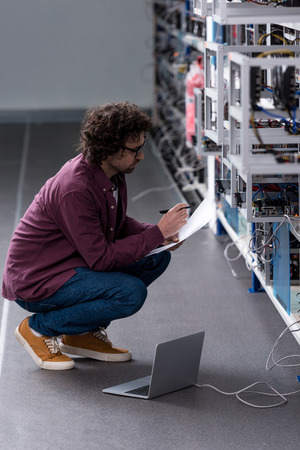 serious computer engineer working while sitting on floor at cryptocurrency mining farm Фото со стока