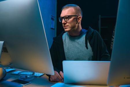 young hacker developing malware in dark room