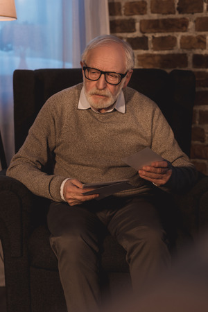 senior  man sitting in armchair, holding old photos and looking away Imagens