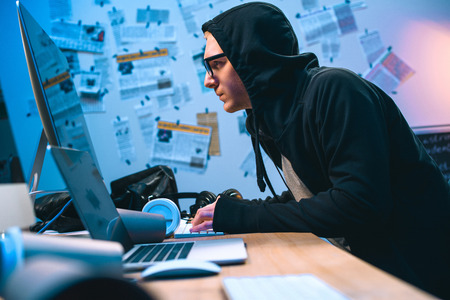 serious hooded hacker working with computer to develop malware Banco de Imagens
